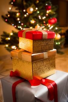 Zbliżenie zdjęcie złotych i czerwonych pudełek na prezenty pod choinką