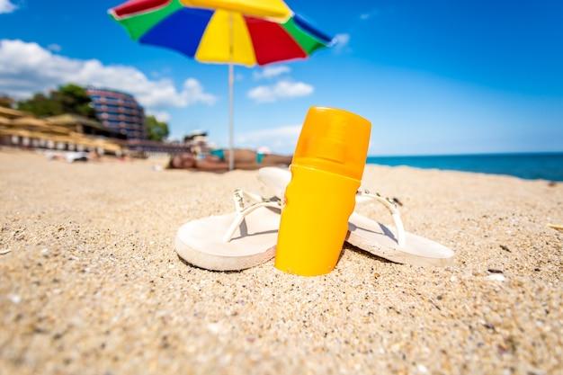 Zbliżenie zdjęcie żółtego balsamu do opalania i klapki leżące na piaszczystej plaży