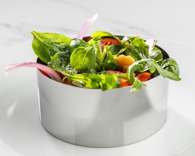 Zbliżenie zdrowej sałatki w układzie okrągłej postaci metalu