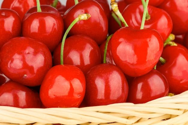 Zbliżenie zdrowych i soczystych czerwonych wiśni w wiklinowym koszu