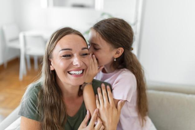 Zbliżenie zdumiona matka słyszy niesamowite wieści od małej córeczki, dziewczynka dzieli się sekretem, mówiąc coś interesującego, podczas gdy mama otwiera usta czuje się zaskoczona, zaufanie, powiernik, zabawna koncepcja