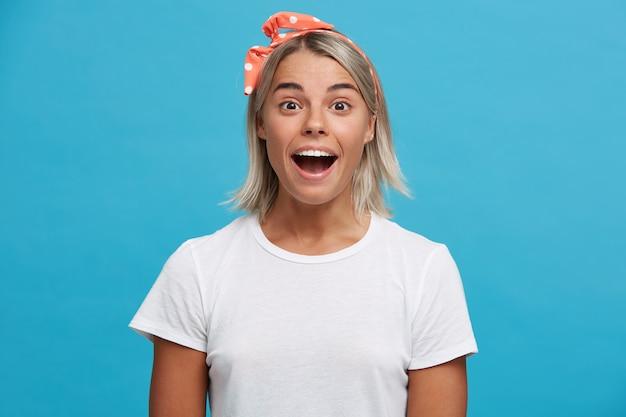 Zbliżenie zdumiony śliczna blondynka młoda kobieta z otwartymi ustami nosi białą koszulkę
