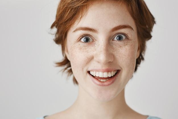 Zbliżenie zdziwiona i podekscytowana uśmiechnięta ruda dziewczyna wyglądająca na zdumionego