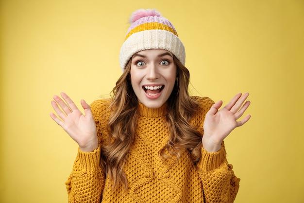 Zbliżenie zdziwiona podekscytowana zdziwiona zdumiona atrakcyjna kobieta krzycząca radośnie podnosząca ręce zdziwiona zdumiona wygrana na loterii usłyszy niesamowite doskonałe wieści, świętująca uśmiechnięta szeroko, żółte tło