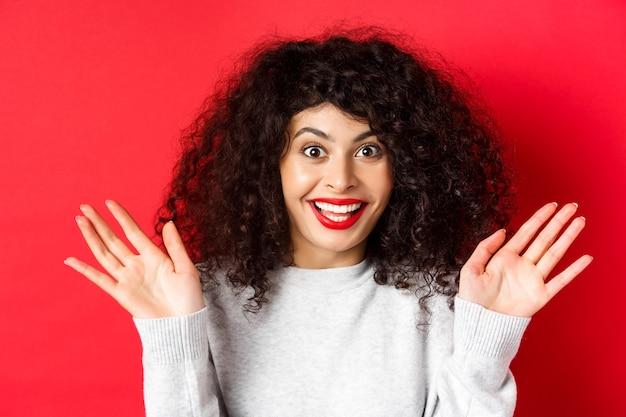 Zbliżenie zdziwionej i szczęśliwej kobiety, która słyszy wspaniałe wieści, reaguje na niesamowite wydarzenie, podnosi ręce i krzyczy radości, uśmiecha się rozbawiony, stoi na czerwonej ścianie.