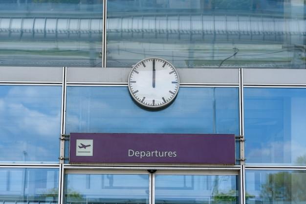 Zbliżenie zegara nad zamkniętymi szklanymi drzwiami lotniska ze znakiem odlotów