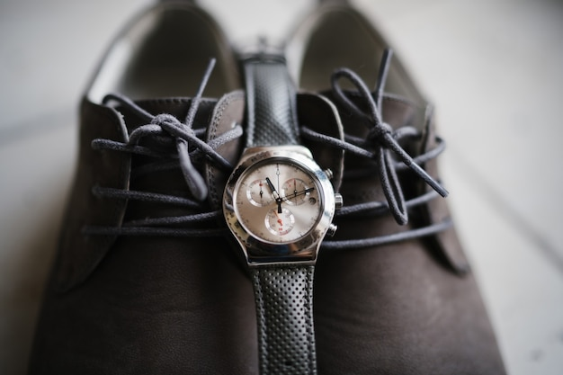 Zbliżenie: zegarek na brązowych butach.