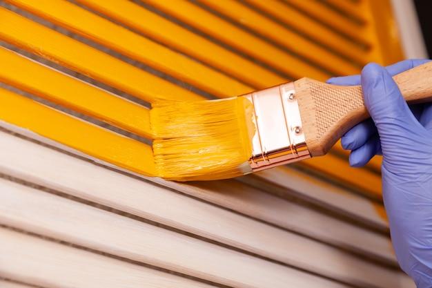 Zbliżenie żeńska ręka w purpurowej gumowej rękawiczce z pędzlem maluje naturalne drewniane drzwi z pomarańczową farbą. kolorowe jasne kreatywne wnętrze. jak malować drewnianą powierzchnię. wybrany fokus