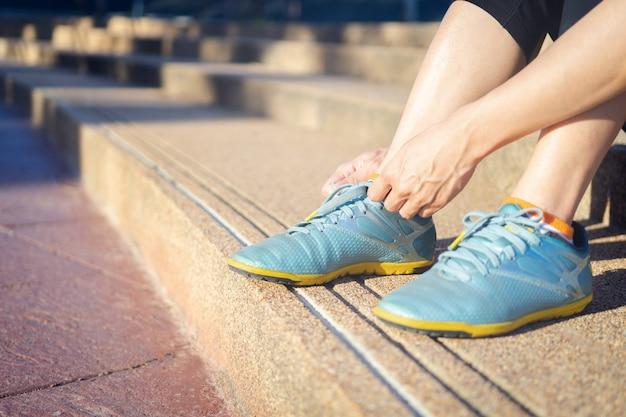 Zbliżenie żeński sport sprawności fizycznej biegacz przygotowywa dla jogging outdoors.