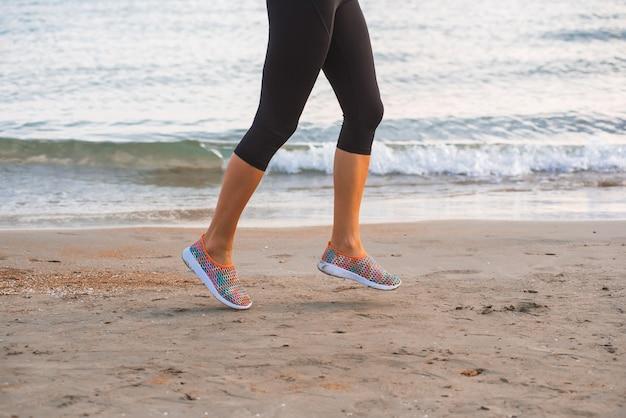 Zbliżenie żeńskie nogi biega na plaży przy wschodem słońca w ranku