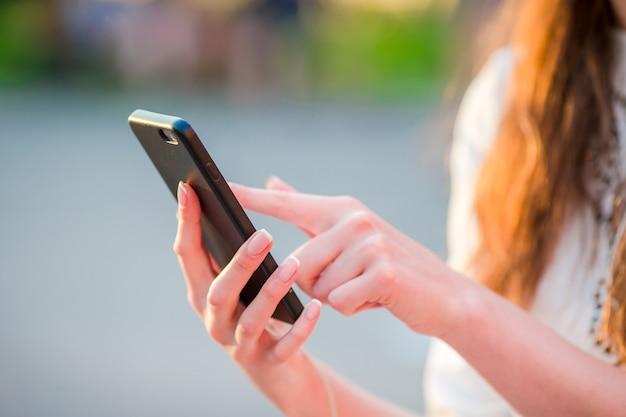 Zbliżenie żeńskie ręki trzyma telefon komórkowego outdoors na ulicie w wieczór światłach. kobieta używa mobilnego smartphone.