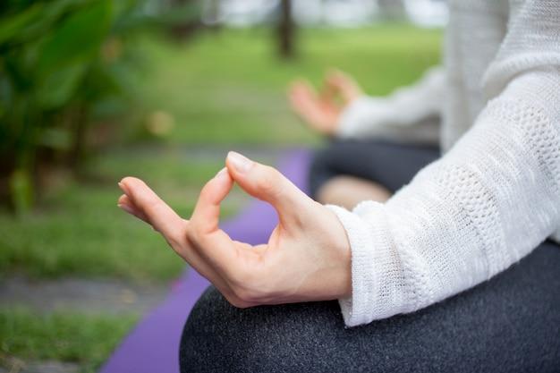 Zbliżenie żeńskiej dłoni medytuje na zewnątrz pomieszczeń