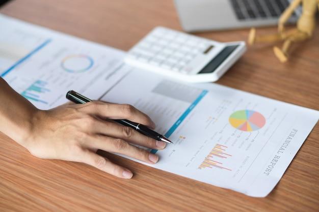 Zbliżenie zespołu analityków pracującego nad raportem finansowym z kalkulatorem i laptopem na stole