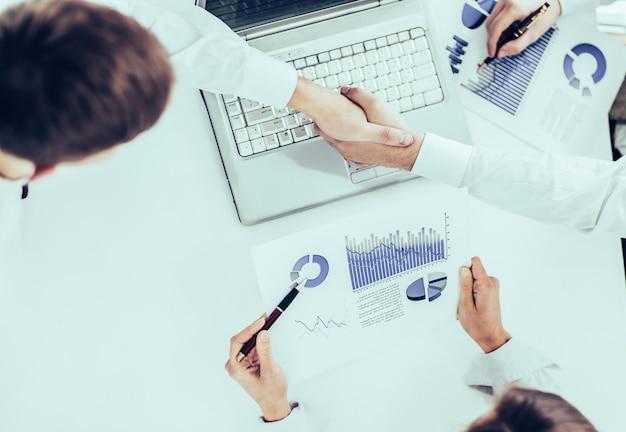 Zbliżenie zespołu biznesowego korzystającego z tabletu cyfrowego, pracującego z harmonogramem finansowym rozwoju firmy