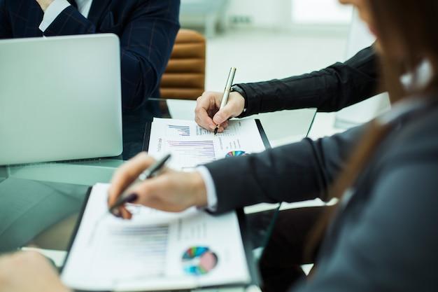 Zbliżenie zespołu biznesowego omawiającego wykresy finansowe