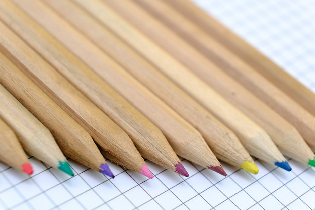 Zbliżenie zestaw kolorowych ołówków na kartce papieru w kratkę notebooka do rysunku. powrót do koncepcji szkoły.