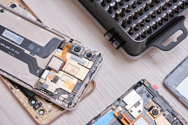 Zbliżenie zestawu końcówek do śrubokrętów w czarnym pudełku, rękawiczek, zepsutych smartfonów oraz zestawu narzędzi do wymiany szkła telefonu i tabletu