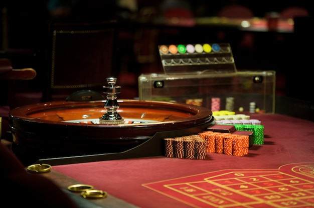 Zbliżenie żetonów i ruletka w kasynie na czerwonym stole