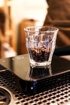 Zbliżenie ziarna kawy wewnątrz kieliszka na cyfrowej skali wagi.