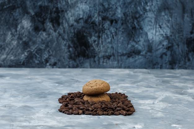 Zbliżenie ziarna kawy z ciasteczkami na granatowym i jasnoniebieskim tle marmuru. poziomy