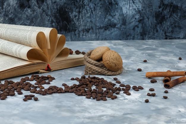 Zbliżenie ziarna kawy z książką, cynamonem, ciasteczkami, linami na ciemnym i jasnoniebieskim tle marmuru. poziomy