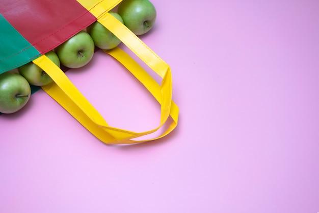 Zbliżenie zieleni jabłka w multicolor ponownie używanej plasti torbie. reklama kampanii z recyklingu i koncepcji zdrowego trybu życia. purpurowe tło.