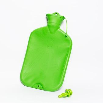 Zbliżenie: zielona butelka gorącej wody medycznej.