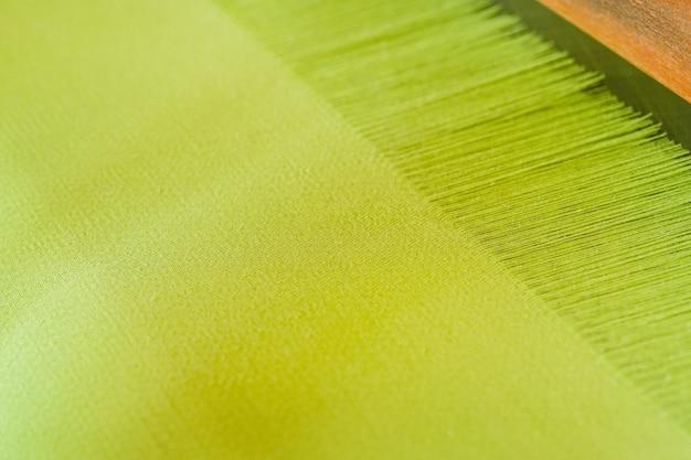Zbliżenie zielona przędza na krośnie tkanie rodzimej bawełny przy użyciu krosna tkackiego