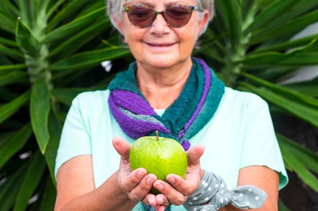 Zbliżenie zielone jabłko w rękach starszej uśmiechniętej kobiety z szalikiem i okularami przeciwsłonecznymi. pojęcie zdrowego odżywiania i diety