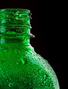Zbliżenie zielonej plastikowej butelki na wodę na czarno