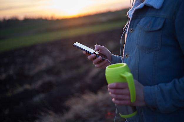 Zbliżenie zielony kubek z kawą i smartfonem w rękach człowieka o zachodzie słońca na świeżym powietrzu