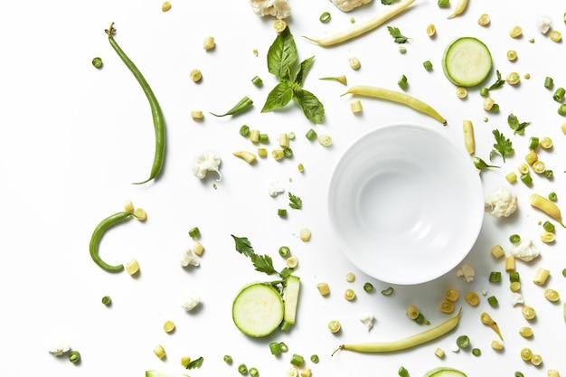Zbliżenie zielonych warzyw i owoców na talerzu do białego stołu. zdrowe odżywianie i jedzenie dla wegan