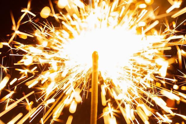 Zbliżenie złocistych, rozmytych iskier płonących w ciemności w świetle świątecznych świec