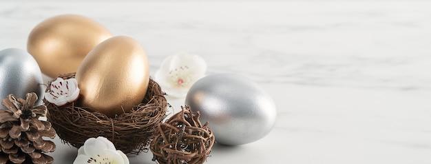 Zbliżenie złote i srebrne pisanki w gnieździe z kwiatem białej śliwki na jasnym tle biały drewniany stół.