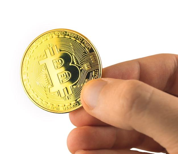 Zbliżenie złotego bitcoina w ręku na białym tle, zdjęcie monety kryptowaluty