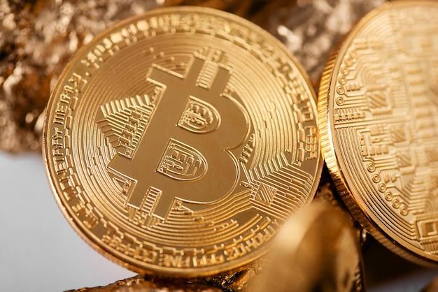 Zbliżenie złoty bitcoin jako główny cryptocurrency z złocistymi gomółkami zamazuje na tle.