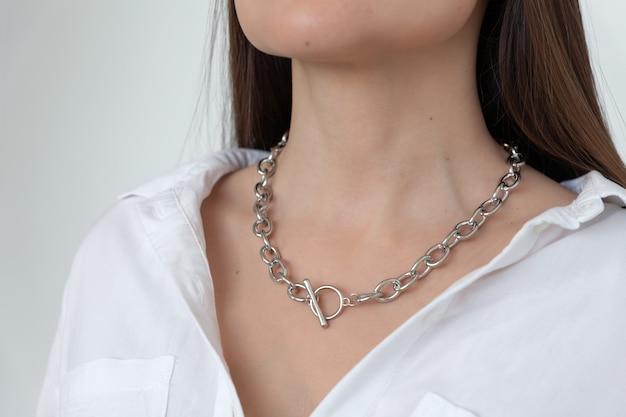 Zbliżenie złoty łańcuch na modelowej brunetce z długimi włosami, metalowy naszyjnik, biały dekolt koszuli