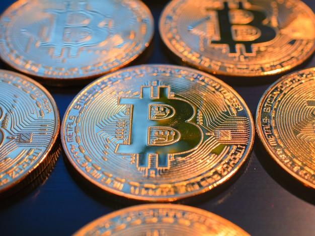 Zbliżenie złotych bitcoinów na czarnym tle. makro niski kąt strzału z selektywnym naciskiem na główną monetę. koncepcja wirtualnego złota