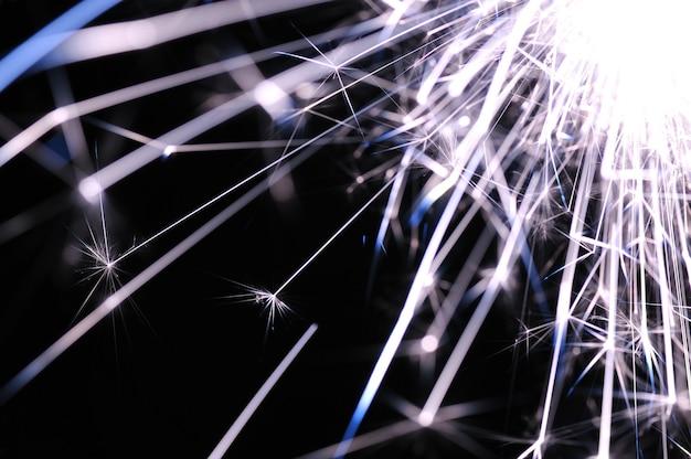 Zbliżenie złotych iskier płonącego ognia na czarnej scenie na cześć święta