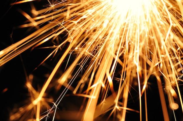 Zbliżenie złotych iskier płonącego ognia na czarno na cześć święta