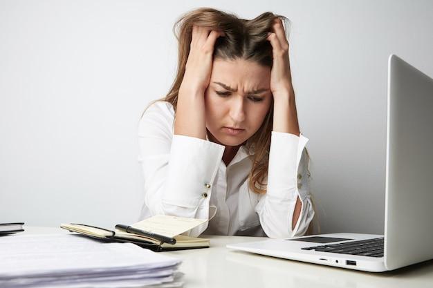 Zbliżenie: zmęczona piękna młoda kobieta w białej koszuli pracuje na laptopie nad pustym światłem.
