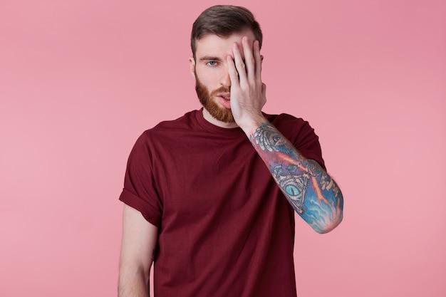 Zbliżenie zmęczony i rozczarowany młody brodaty mężczyzna z wytatuowaną ręką, obejmuje część twarzy ręką. pojedynczo na różowym tle.