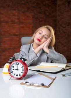 Zbliżenie zmęczony inżynier kobieta siedzi za swoim miejscem pracy