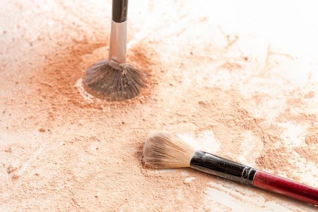 Zbliżenie zmiażdżonego mineralnego połyskującego proszku w złotym kolorze z pędzlem do makijażu