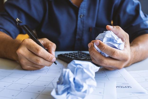 Zbliżenie zmięty papier na stole z nieszczęśliwym biznesmenem brak pomysłów