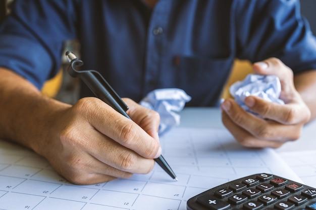 Zbliżenie zmięty papier na stole z nieszczęśliwym biznesmenem brakiem pomysłów. nieostrość i nadmierne światło w tle