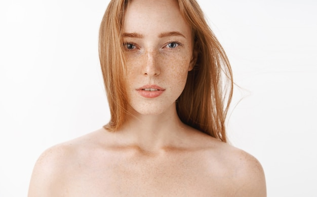 Zbliżenie zmysłowej kobiecej i atrakcyjnej rudowłosej kobiety stojącej nago z lekko otwartymi ustami i marzycielskim romantycznym wyrazem twarzy cieszącej się ciepłą kąpielą po pracy