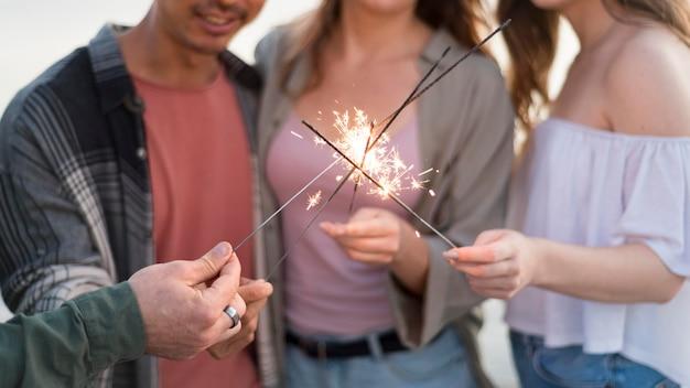 Zbliżenie znajomych posiadających fajerwerki