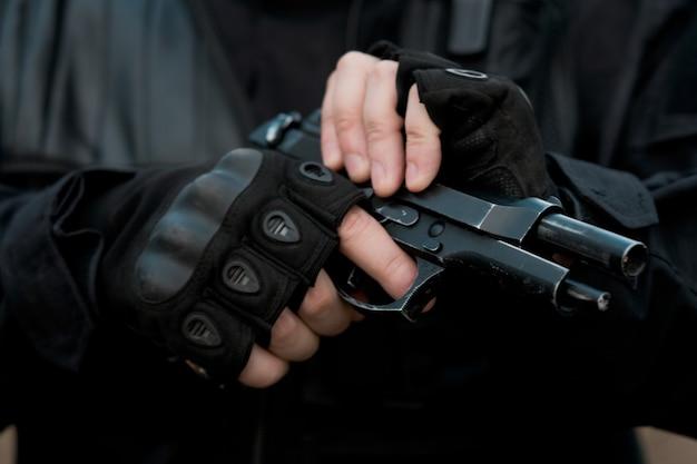 Zbliżenie żołnierza sił specjalnych w czarnym mundurze przeładowującym pistolet