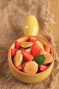 Zbliżenie żółta miska pełna tiny pancake lub popularna jako zbożowy naleśnik, popularna wirusowa przekąska podczas kwarantanny w 2020 r. podana nad jutowym brązowym tłem, wersja pionowa